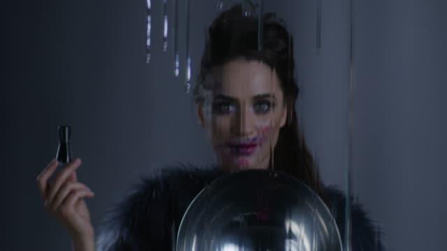 vídeos de stock, filmes e b-roll de morena alta moda modelo em pele desgastando do estágio make-up possui uma placa de prata em uma mão e garrafa de esmalte preto no outro. vídeo de moda. - bandeja de prata
