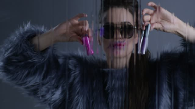 brunette high fashion model wearing sunglasses and fur holds pink nail polish in one hand and violet lipstick in another. fashion video. - pink lipstick stock videos and b-roll footage
