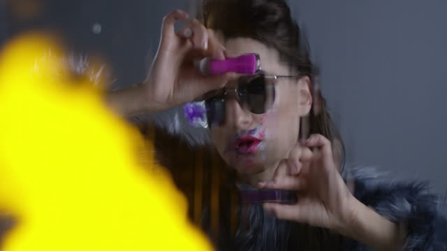 brunette high fashion model wearing sunglasses and fur holds pink nail polish in one hand and violet lipstick in another. lames of fire. fashion video. - pink lipstick stock videos and b-roll footage