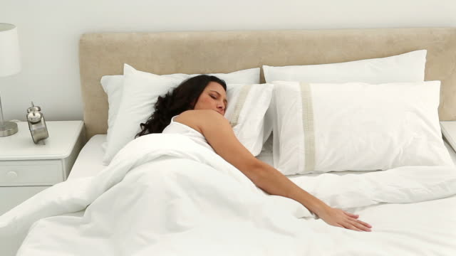 Brunette holding a pillow while she sleeps