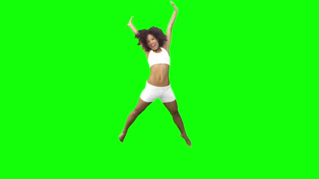 brunette performing a star jump in slow motion - star jump stock videos & royalty-free footage