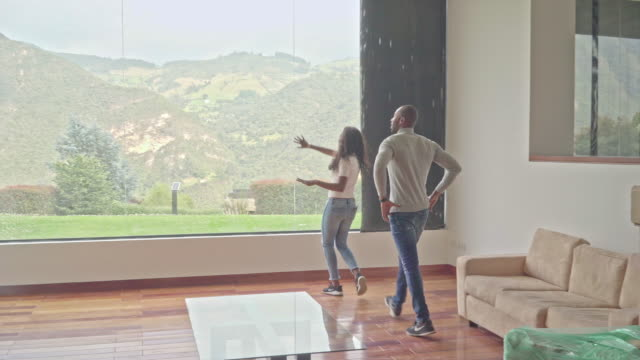 vídeos de stock e filmes b-roll de brunette latin couple hug each other and enjoy their beautiful home looking from the large window of their living room - de corpo inteiro