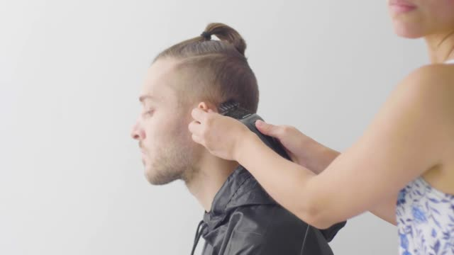 a brunette latin woman shaves a white caucasian man's beard with an electric razor - caucasian appearance stock videos & royalty-free footage