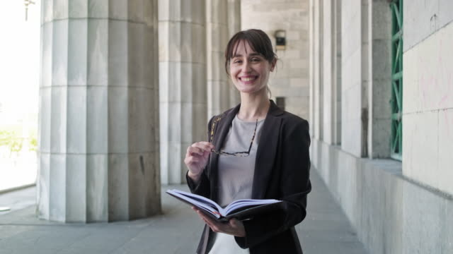 brunette law student standing at entrance to school building - reading glasses stock videos & royalty-free footage