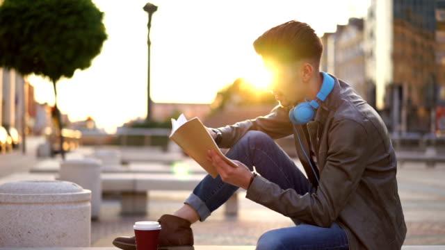 vídeos y material grabado en eventos de stock de libro de lectura hombre morena al aire libre - bien parecido