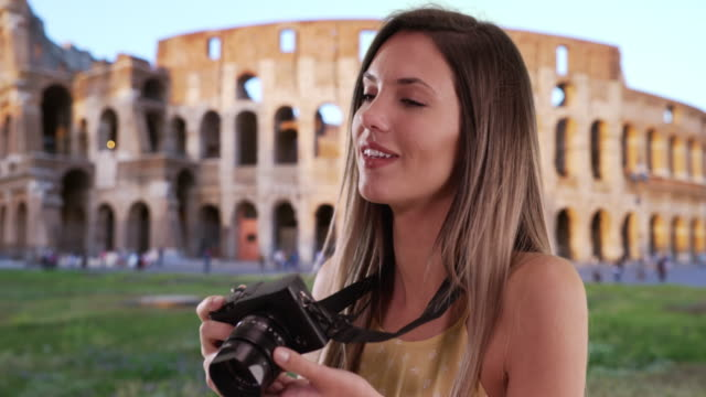 Brunette millennial in her 20s shooting pictures with camera by Coliseum in Rome