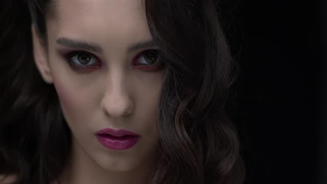 vidéos et rushes de brunette avec le maquillage fumé et les lèvres lumineuses regarde le visage plein directement dans l'appareil-photo. - sensualité