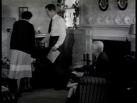 brunette woman entering neighbor's living room talking w/ husband senior male saying husband should go upstairs see what doctor says - 1948 stock-videos und b-roll-filmmaterial