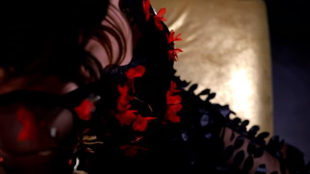 vídeos de stock, filmes e b-roll de morena de vestido preto, sentado no sofá colorido ouro - de pernas cruzadas