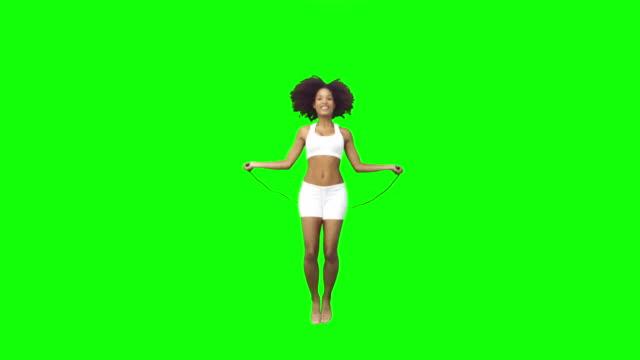 vídeos y material grabado en eventos de stock de brunette woman playing in slow motion with a skipping rope - fondo verde