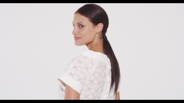 vídeos de stock e filmes b-roll de brunette woman in white dress turns 180 degrees to camera and smiles - vestido branco