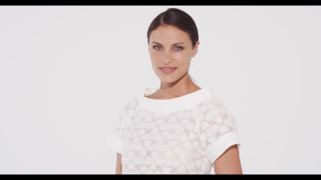 brunette woman in white dress turns 180 degrees to camera smiling - 白のドレス点の映像素材/bロール