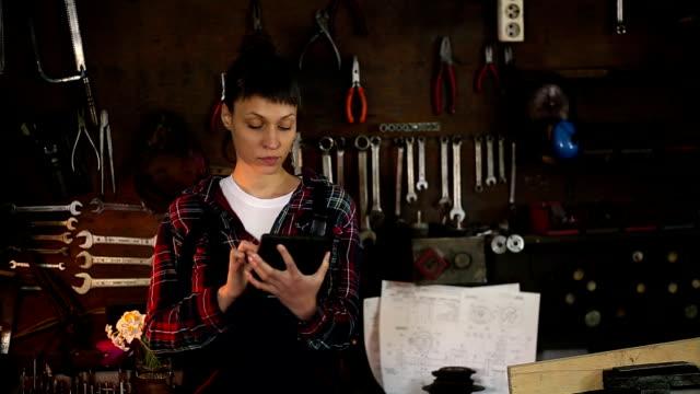 Brunette vrouw, werktuigbouwkundig ingenieur kijken naar Tablet In Workshop