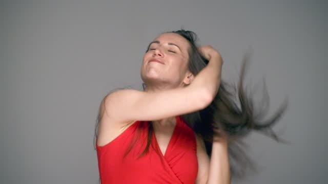 vidéos et rushes de brunette femme secouer cheveux - robe rouge