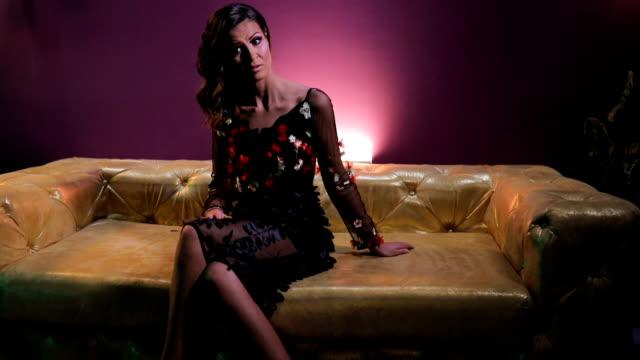 vídeos y material grabado en eventos de stock de mujer morena sentada en el sofá de color oro - con las piernas cruzadas