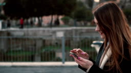 Brunette woman walking in the park and using touchscreen technology at smartphone. Girl spending time outdoors