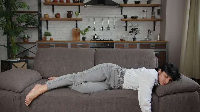 vídeos de stock e filmes b-roll de brunette woman with short hair falls down exhausted on sofa - exaustão