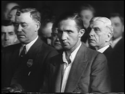 vidéos et rushes de bruno hauptmann standing with lawyers in courtroom / lindbergh kidnapping / newsreel - 1935