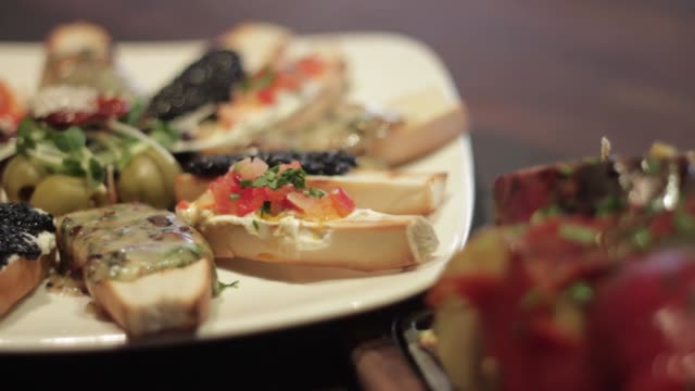 bruschettas with caviar smoked salmon and brie cheese grilled vegetables at the barbecue - ブリーチーズ点の映像素材/bロール
