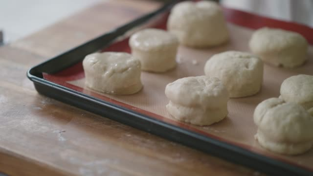 brush egg on the scone for baking - baking tray stock videos & royalty-free footage