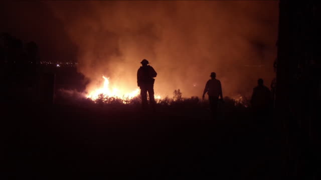 Brush fire threatens 300 homes / Firetruck and firefighters / Firefighter silhouette and forest fire