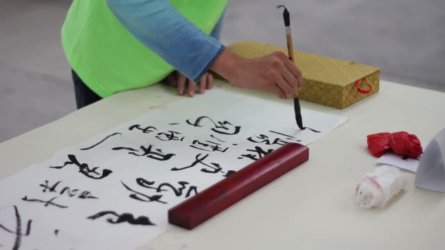 ms brush writing chinese calligraphy in black ink on rice paper/xian,shaanxi,china - washi paper stock videos & royalty-free footage