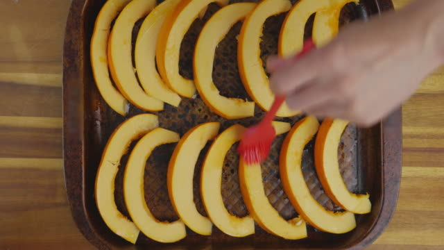 brushing olive oil on pumpkin wedges - baking tray stock videos & royalty-free footage