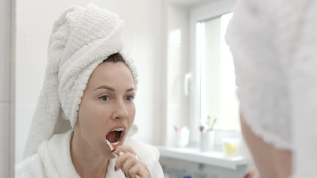 brushing teeth pretty woman with towel on head with a toothbrush shot on red epic - toothbrush stock videos & royalty-free footage