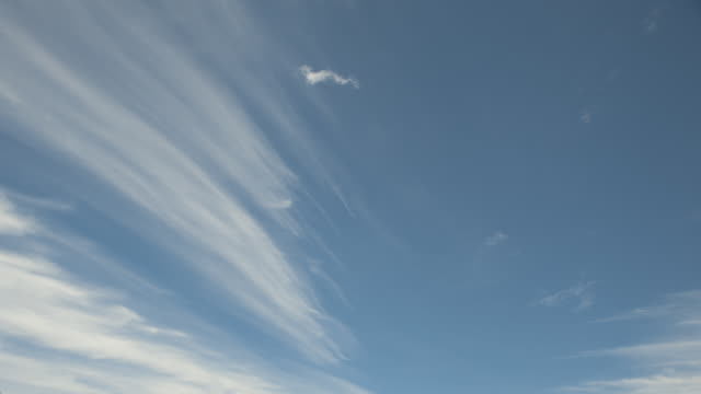 Brush-stroke-like clouds drift through the sky.
