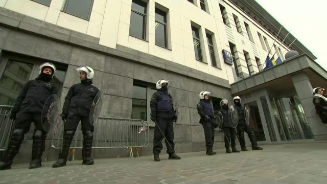 vidéos et rushes de police close down protest marches riot police stand guard in molenbeek town square - belgique
