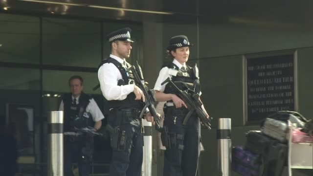 security stepped up / uk reaction england london heathrow airport int police officers along walkway armed police officers standing guard outside... - terrorism stock videos & royalty-free footage