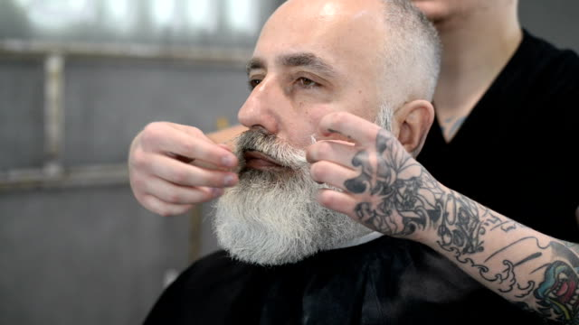 brutal barber clipper mows bearded adult senior hipster - beard stock videos & royalty-free footage