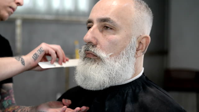 brutal barber clipper mows bearded adult senior hipster - barber shop stock videos and b-roll footage