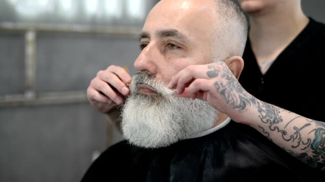 brutal barber clipper mows bearded adult senior hipster - barber shop stock videos & royalty-free footage