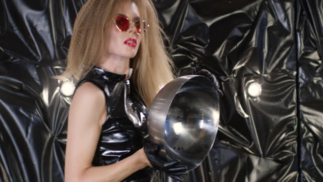 brutal fashion model in black latex dress holds silver platter. fashion video. - silver platter stock videos and b-roll footage