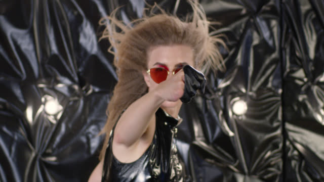 Brutal high fashion blond model is boxing in black leather gloves. Fashion video.