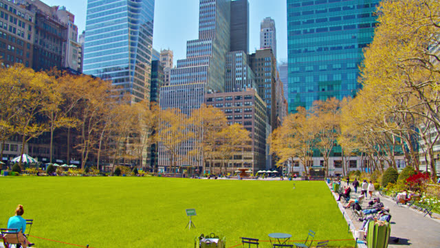 bryant park. empty green area. new yorkers sit at tables at leisure. relaxation and tranquility. - bryant park stock videos & royalty-free footage