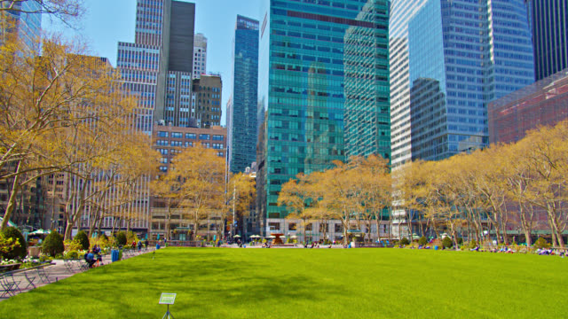 bryant park. empty large green lawn. people rest at leisure. financial buildings. new york - bryant park stock videos & royalty-free footage