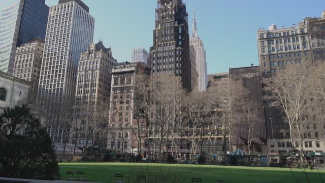 vidéos et rushes de bryant park, l'une des destinations populaires pour les new-yorkais et les touristes, est calme et désert en raison de l'épidémie covid-19. - empire state building