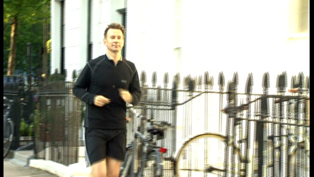 david cameron backs jeremy hunt ext jeremy hunt jogging along road and up to his house - 政治家 ジェレミー ハント点の映像素材/bロール