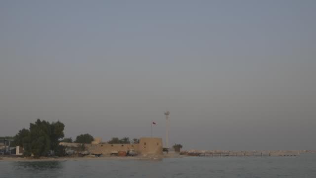bu maher fort. view of bu maher fort in muharraq from a boat. - ペルシャ湾点の映像素材/bロール