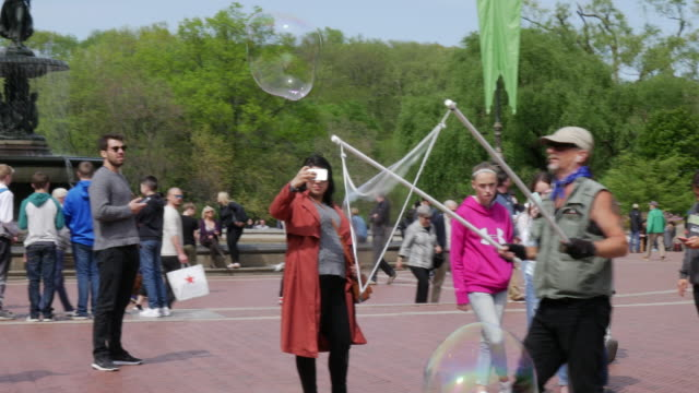 bubble playing in central park, new york city - bubble wand stock videos & royalty-free footage