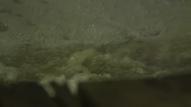 bubbles and foam form on the top of a vat of beer as it churns. - milk churn stock videos & royalty-free footage
