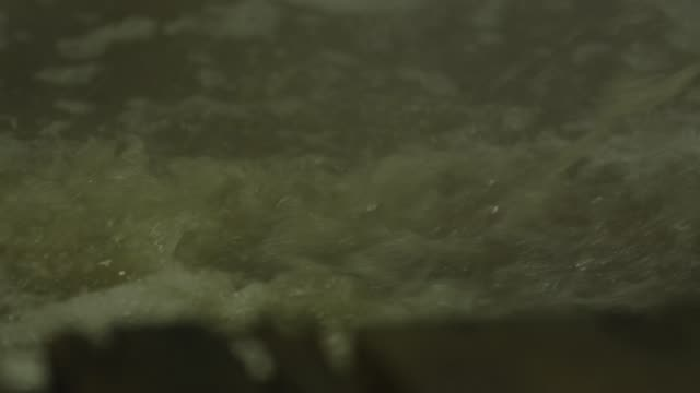 bubbles and foam form on the top of beer as it churns in a vat. - milk churn stock videos & royalty-free footage