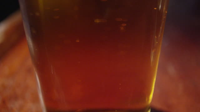 bubbles floating to foam surface of beer - amber stock videos & royalty-free footage