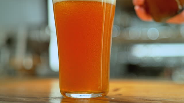 slo mo ds bubbles flowing as beer is being poured into a glass - beer glass stock videos & royalty-free footage