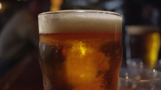 bubbles in glass of beer - pint stock-videos und b-roll-filmmaterial