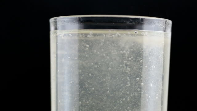 bubbles of calcium and vitamin in pill put into a glass of water. - calcare video stock e b–roll