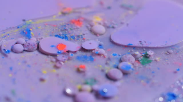 stockvideo's en b-roll-footage met bubbles of purple paint burst and spill out into a pool of water. - versmelten