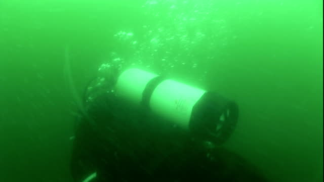 bubbles rise from scuba diver in murky, green water. - aqualung diving equipment stock videos & royalty-free footage
